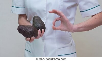 nutritionist doctor healthy lifestyle concept - holding organic avocado