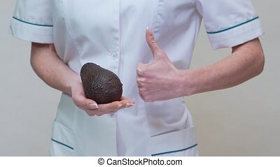 nutritionist doctor healthy lifestyle concept - holding organic avocado.