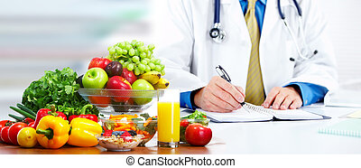 Nutritionist doctor man with vegetables working in the ...