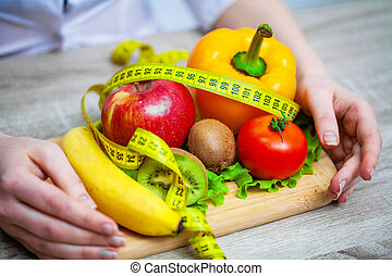 Nutritionist holding fresh fruits and vegetables for healthy diet