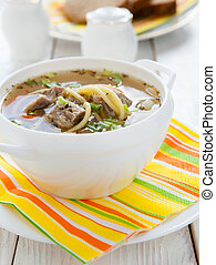 nutritious meat soup with pasta in a white tureen