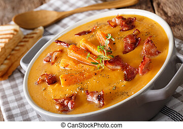 nutritious soup made of sweet potato with bacon and thyme close-up. horizontal
