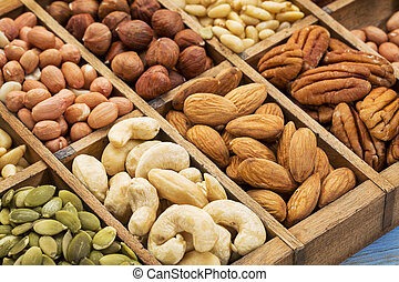 nuts and seed collection (cashew, pecan, hazelnut, pine nuts, peanut, pumpkin) in an old typesetter wooden drawer