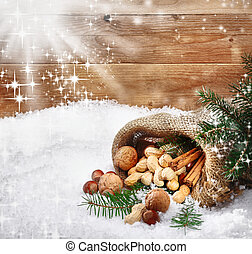 Festive Christmas nuts cascading from an open burlap sack onto winter snow with sparkling snowflakes caught by the sun in front of wooden boards with copyspace