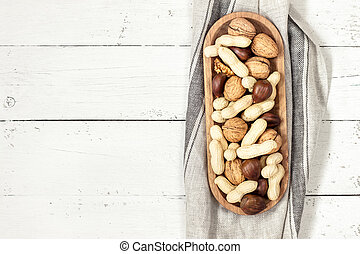 Nuts in a bowl on a white wooden background. Copy space