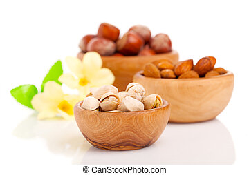 Nuts in a wooden bowl on a white background