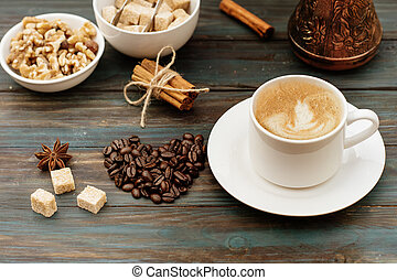 Nuts in the bowl, coffeepot, heart-shaped coffee beans, cinnamon, anise, sugar, and cap of coffee on wooden background