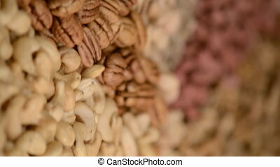 Nuts mix in a canvas bag in table. Ten kinds of nuts: pecan, brazil, cedar, sunflower, hazelnut, almond, peanut, walnut, pistachio, cashew. The nut mix rotates on the turntable