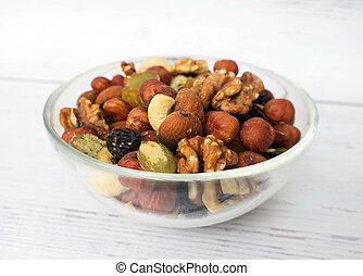 Nuts, seeds and dried fruits in a glass bowl on a wooden light background