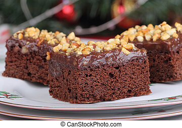 Chocolate fudge brownies on a plate with Christmas decorations in background
