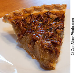Pecan pie covered in nuts on a white plate