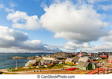 Nuuk city old harbor fjord panorama with clouds over the blue sky in the background, Greenland
