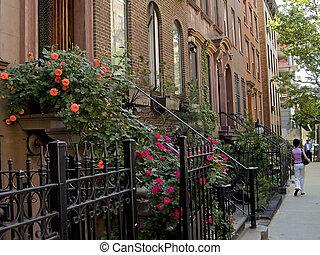 A nice New York City neighborhood of well kept brownstone homes.