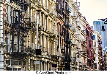 New York City view of exterior facade on ornate old apartment building residence with fire escapes seen from lower Manhattan, NYC Soho.