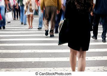 Bustle of pedestrians NYC at crosswalk