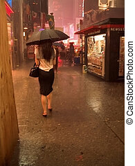 NYC Rain 2 - A lady with an umbrella walks in the rain at...