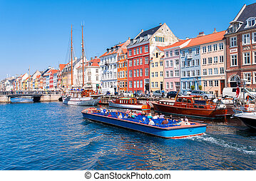COPENHAGEN - MAY 18: Nyhavn in the centre of Copenhagen on May 18, 2013. Nyhavn is old waterfront and canal district in Copenhagen. It is lined by coloured houses and restaurants.
