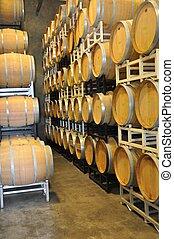 Oak Wine Barrel - Stacked oak wine barrels in winery cellar.