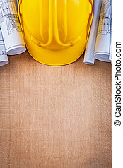 Oaken wooden board with yellow hard hat and blueprints construct