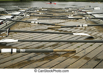 Oars On A Dock - Two racing shells by the dock with oars at...