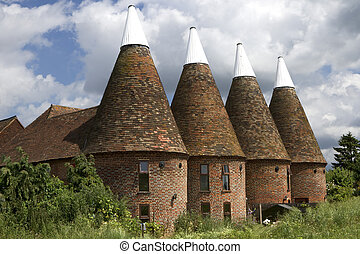 View of the four tops of a large oasthouse in Kent, England.