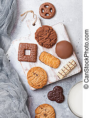 Oat and chocolate cookies selection with glass of milk on wooden board on stone kitchen table background.