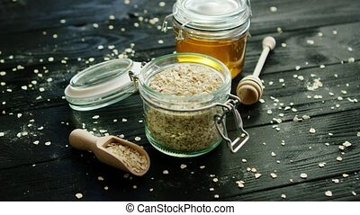 Oat and honey in glass jars - From above view of oat in...