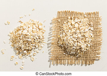 Oat cereal grain. Close up of grains spreaded over white table.