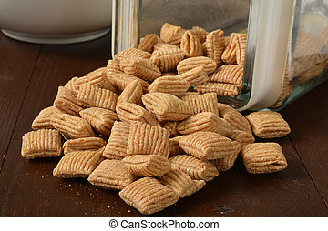 Squares of oat cereal spilling out of a glass container