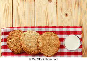 Oat cookies and glass of milk on wooden table