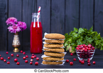 Oat cookies, cranberry juice and raw cranberry on black wooden background, close up
