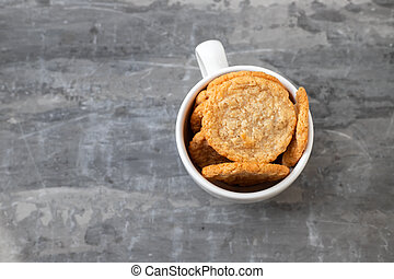 oat cookies in the white cup on ceramic background