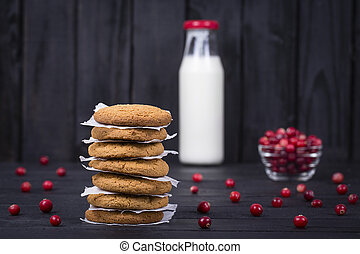 Oat cookies, milk and raw cranberry on black wooden background, close up