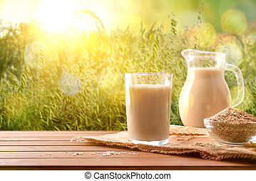Oat drink in glass and cereal flakes on wood table in nature. Horizontal composition. Front view