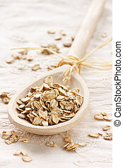 Raw thick rolled oats in a wooden spoon.