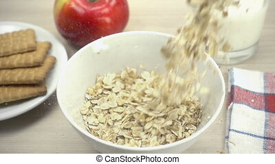 Oat flakes falling into white bowl in slow motion. Apple,...
