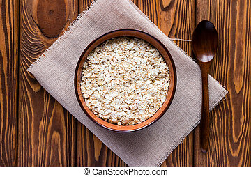 oat flakes in a bowl on a napkin and a wooden spoon