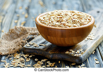 Oat flakes in a wooden bowl.
