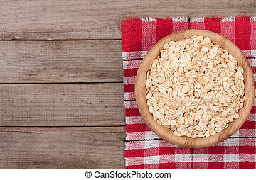 Oat flakes in a wooden bowl on old wooden background with copy space for your text. Top view