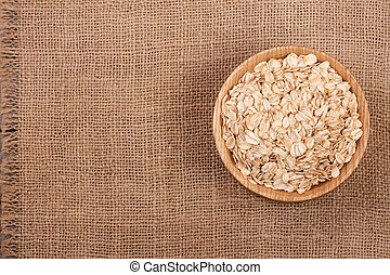 Oat flakes in a wooden bowl on sackcloth with copy space for your text. Top view