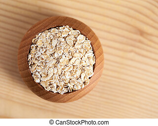 Oat flakes in a wooden bowl on the wooden table