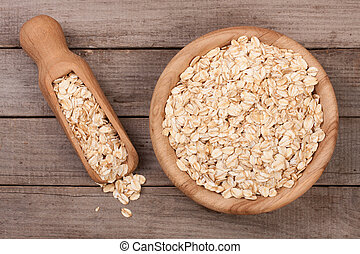 Oat flakes in a wooden bowl with a scoop on an old wooden background