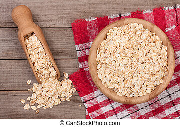 Oat flakes in a wooden bowl with a scoop on old wooden background
