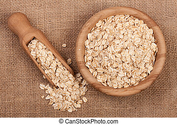 Oat flakes in a wooden bowl with a scoop on sackcloth