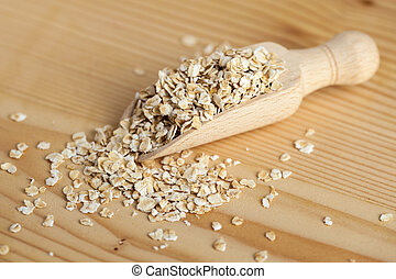 Oat flakes in a wooden bowl with a scoop on the wooden board