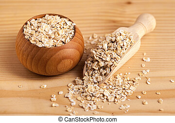 Oat flakes in a wooden bowl with a scoop on the wooden table