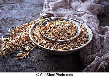 Oat flakes in bowl and spikelets