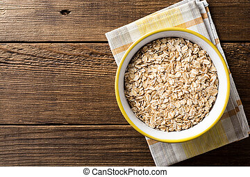 Oat flakes in bowl on dark wooden table