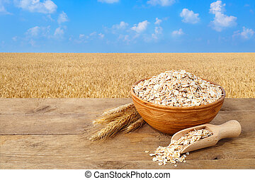 Oat flakes in bowl with field on the background
