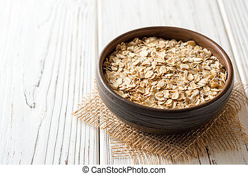 Oat flakes in ceramic bowl on white wooden table